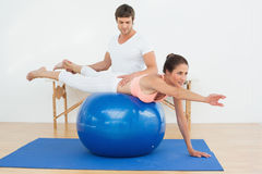 Physical therapist assisting young woman with yoga ball Royalty Free Stock Image