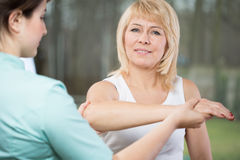 Physical therapist diagnosing painful arm. Young female physical therapist diagnosing painful arm Stock Image