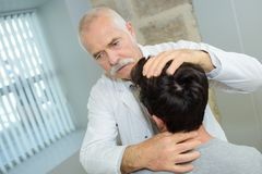 Physical therapist examines patients neck. Physical therapist examines a patients neck Royalty Free Stock Photo