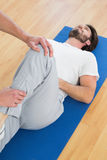 Physical therapist examining mans leg Stock Photo