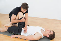 Physical therapist examining young mans leg Stock Photo