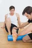 Physical therapist examining a young mans leg Stock Images
