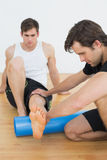 Physical therapist examining a young mans leg Royalty Free Stock Image