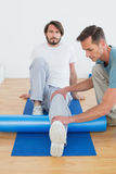 Physical therapist examining young mans leg Stock Photos