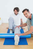 Physical therapist examining young mans leg Stock Images