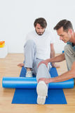 Physical therapist examining young mans leg Royalty Free Stock Photos