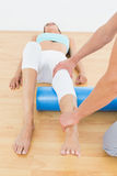 Physical therapist examining a young womans leg Royalty Free Stock Images
