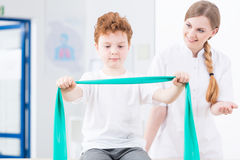 Physical therapist exercising with boy