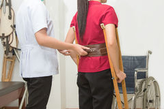 Physical therapist helping patient to walk using crutches. In hospital, physical rehabilitation therapy Stock Photography