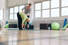 Physical therapist helping senior woman at gym. Senior women bending forward and touching her toes being helped by personal trainer at health club. Elder women Stock Image