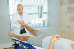 Physical therapist massaging feet client. Physical therapist massaging feet of client Stock Images