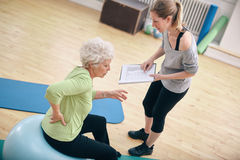 Physical therapist with old woman at rehab. Senior women sitting on a fitness ball with her female instructor explaining exercise plan at gym. Physical therapist Stock Images