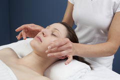Physical therapist practicing a facial massage. Palming facial massage at the spa Royalty Free Stock Photo