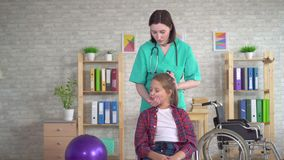 Physical therapist in rehab is doing the treatment on the neck of the girl adolescent. Rehabilitation after injury or paralysis stock video footage