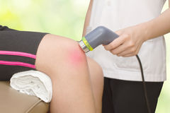 Physical therapist using ultrasound probe on woman patient 's kn Royalty Free Stock Photo