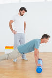 Physical therapist watching young man do push ups Stock Image