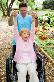 Physical Therapist at Work. Physical therapist helping a disabled senior woman to regain mobility in her upper limbs Royalty Free Stock Photos