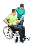 Physical therapist works with patient in lifting hands weights. Young adult in wheelchair Royalty Free Stock Images