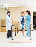 Physical Therapists Assisting Female Patient In stock image