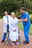Physical therapists helping patient walk. Two physical therapists helping a wheelchair patient to walk outdoors Royalty Free Stock Image