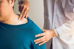 Physical therapists are using their hands to press the clavicle of the patient.  stock photography