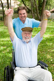 Physical Therapy is Fun. Senior man and his physical therapist having a pleasant outdoor workout Royalty Free Stock Image