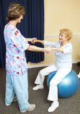 Physical Therapy Workout. Physical therapist using pilates ball to work with senior chiropractic patient Royalty Free Stock Photo