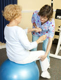 Physical Therapy with Yoga Ball. Senior woman on yoga ball, working with a physical therapist Stock Image
