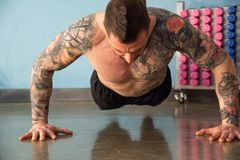 Personal trainer with tattoos performs exercises with his arms raised off the floor stock images