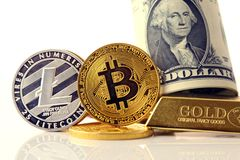 Physical version of Bitcoin and Litecoin, new virtual money. Conceptual image for investors in cryptocurrency, gold and dollars Royalty Free Stock Images