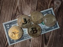 Physical version of Bitcoin new virtual money and banknotes of two dollar. Exchange bitcoin for a dollar. stock photography