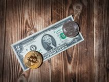 Physical version of Bitcoin, new virtual money, and banknotes of two dollar on a wooden background. Conceptual image for worldwide stock image