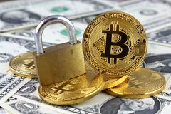 Physical version of Bitcoin new virtual money, golden padlock and banknotes of one dollar Stock Image