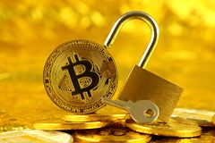 Physical version of Bitcoin new virtual money and golden padlock. Royalty Free Stock Images