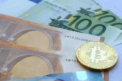Coins of bitcoins on Euro banknotes stock photography