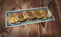 Physical version of Bitcoins, new virtual money, and banknotes of two dollar on a wooden background. Conceptual image for royalty free stock image