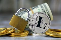 Physical version of Litecoin new virtual money, golden padlock and banknotes of one dollar. Royalty Free Stock Photography