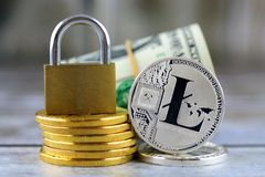 Physical version of Litecoin new virtual money, golden padlock and banknotes of one dollar. Royalty Free Stock Photos