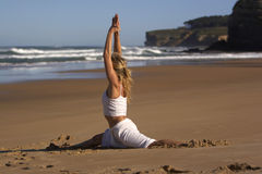 Physical wellness. Woman practicing yoga in the beach Stock Photo