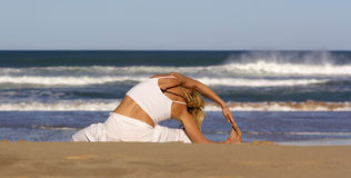Physical wellness. Woman practicing yoga in the beach Stock Photography