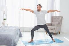 Joyful positive man standing on a yoga mat. Physical workout. Joyful positive man standing on a yoga mat while doing an exercise Royalty Free Stock Photography