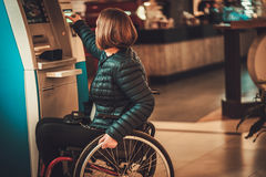 Physically challenged woman near ATM.  Royalty Free Stock Images