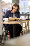 Physically challenged woman reading in a cafe. Physically challenged woman in a cafe Stock Photo