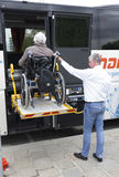 Physically disabled bus accessibility platform. Vienna, Austria - May 1, 2015: A bus driver helps physically disabled person in a wheelchair to board in the bus Royalty Free Stock Image
