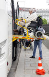 Physically disabled bus accessibility platform. Vienna, Austria - May 1, 2015: A bus driver helps physically disabled person in a wheelchair to board in the bus Stock Images