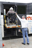 Physically disabled bus accessibility platform. Vienna, Austria - May 1, 2015: A bus driver helps physically disabled person in a wheelchair to board in the bus Stock Photo