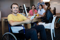 Physically disabled man on wheelchair using tablet in office Royalty Free Stock Photos