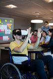 Physically disabled man on wheelchair using VR headset. Physically disabled men on wheelchair using VR headset in office Stock Photos