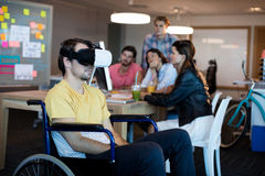 Physically disabled man on wheelchair using VR headset. Physically disabled men on wheelchair using VR headset in office Stock Photography