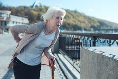Senior lady holding her hands on back while feeling pain Stock Image